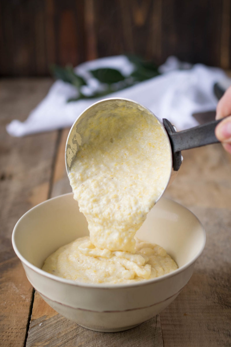 Pouring warm polenta into a white bowl
