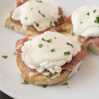 3 pieces of ciabatta bread topped with prosciutto, a poached egg and Parmesan sauce
