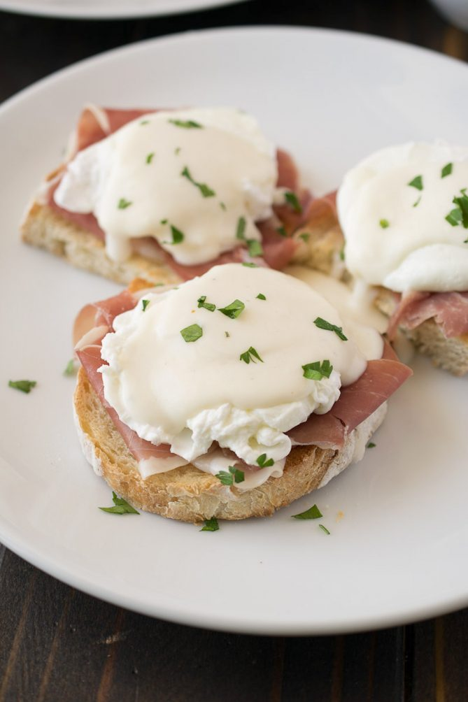 3 English muffins topped with prosciutto, a poached egg and Parmesan sauce
