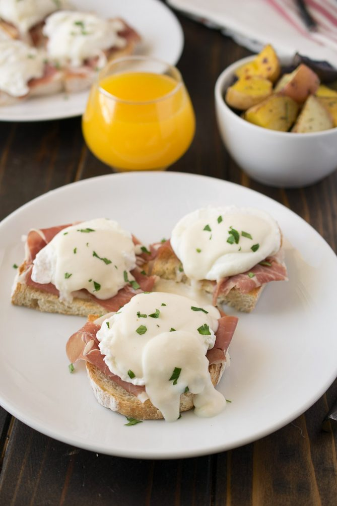 3 Italian eggs Benedict on a plate with a glass of orange juice and potatoes
