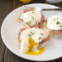 A poached egg on top of prosciutto and ciabatta bread cut open with yellow yolk running out