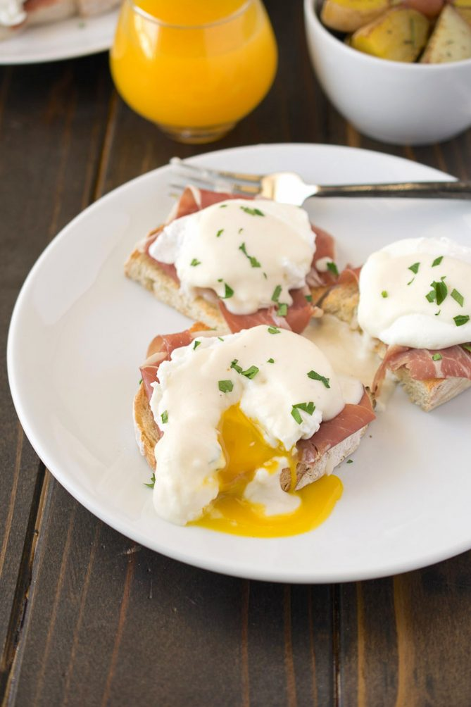 A poached egg on top of prosciutto and an English muffin cut open with yellow yolk running out