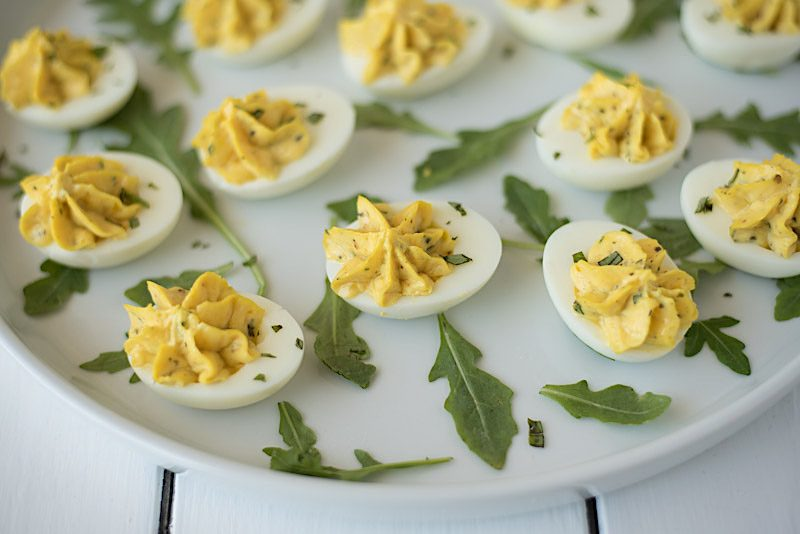 Deviled eggs with the yolks piped on a white plate with fresh arugula