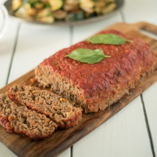 Italian style meatloaf sliced on a serving board with fresh basil leaves