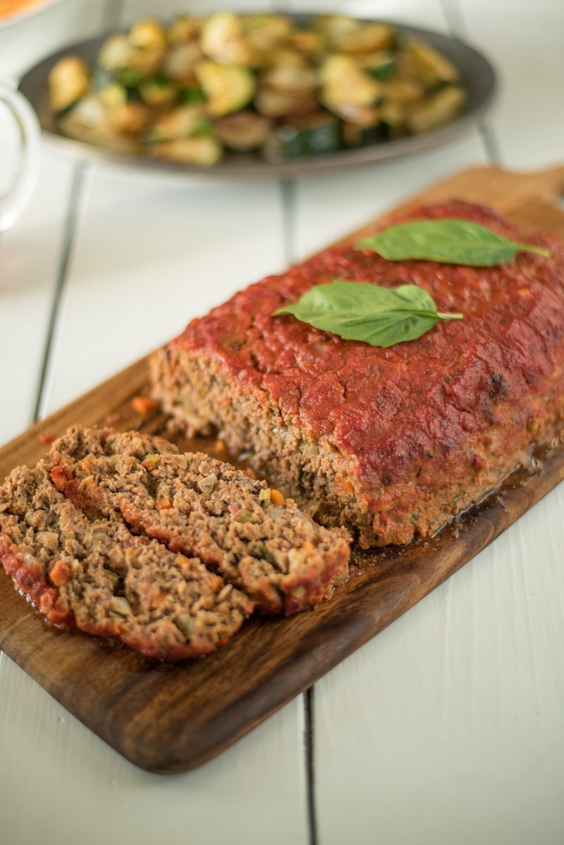 The meatloaf on a wood serving board with 2 slices and vegetables