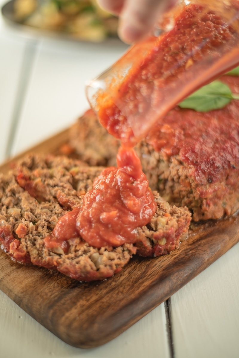 Pouring marinara sauce onto sliced meatloaf