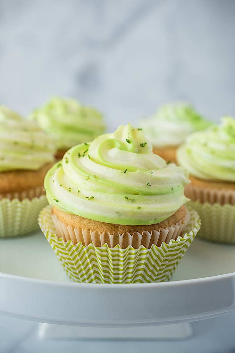 Key lime cupcakes on a white cake stand