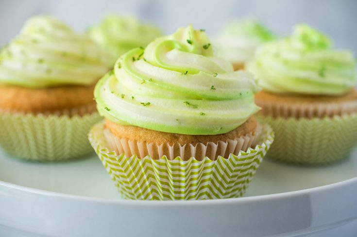 Key lime cupcakes on a cake stand in green and white striped cups