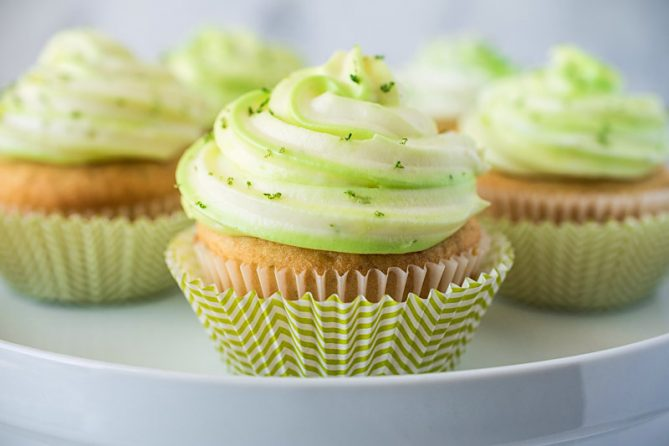 A key lime cupcake in a striped green and white muffin cup