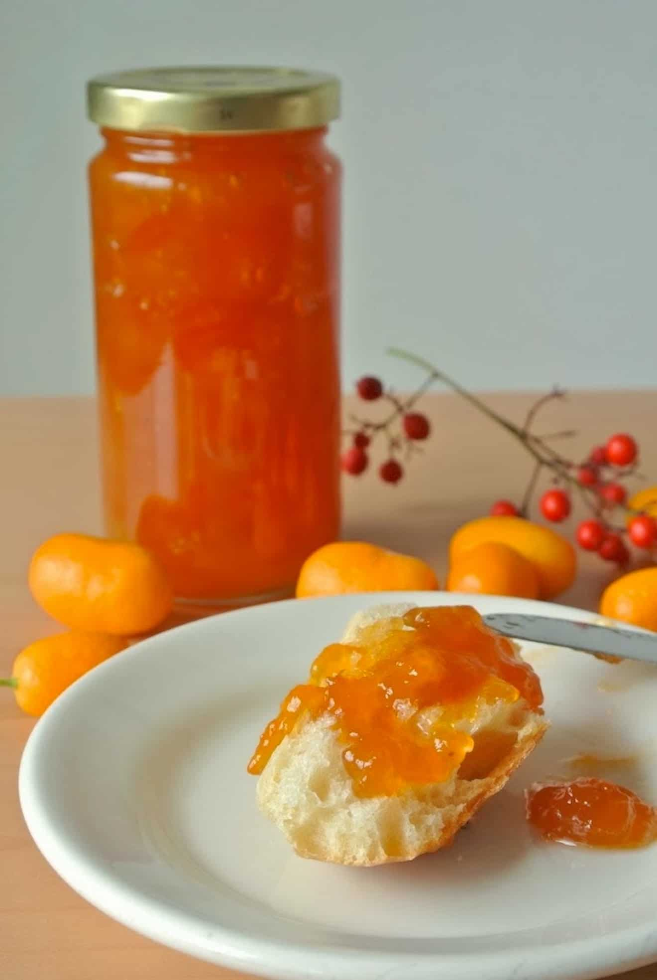 A jar of kumquat marmalade with some spread onto bread