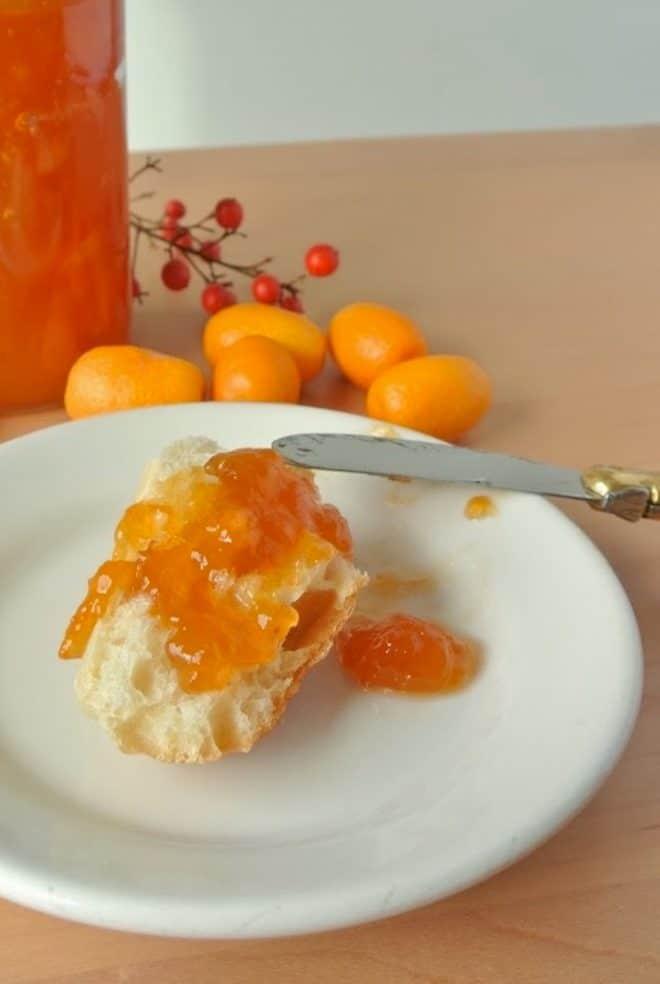 Kumquat marmalade spread onto bread on a plate