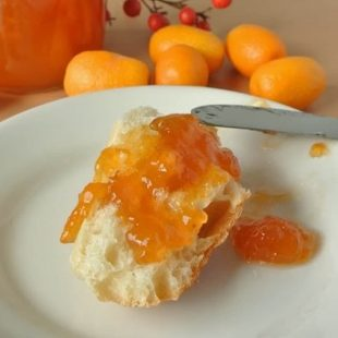 A crusty piece of bread topped with kumquat marmalade
