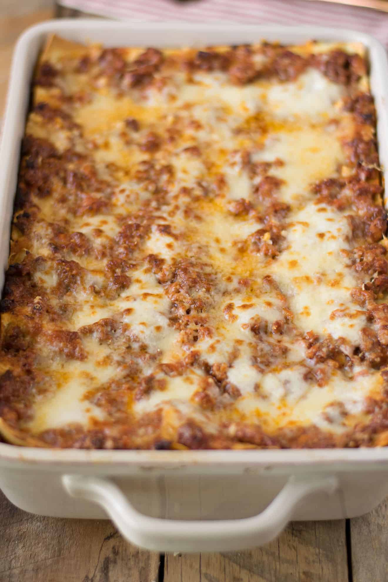 A closeup of a freshly baked Lasagna Bolognese showing the cheesy top