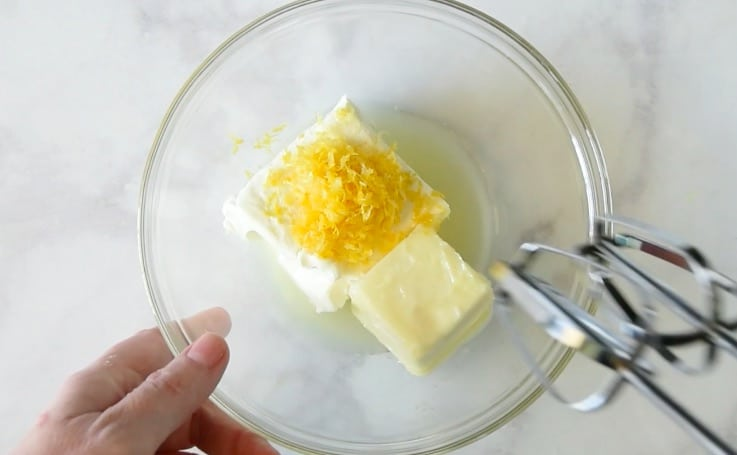 Softened cream cheese, butter and lemon zest being mixed in a glass bowl
