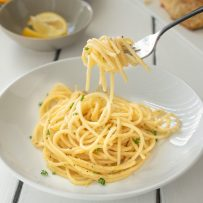A fork full of spaghetti with lemon and pepper