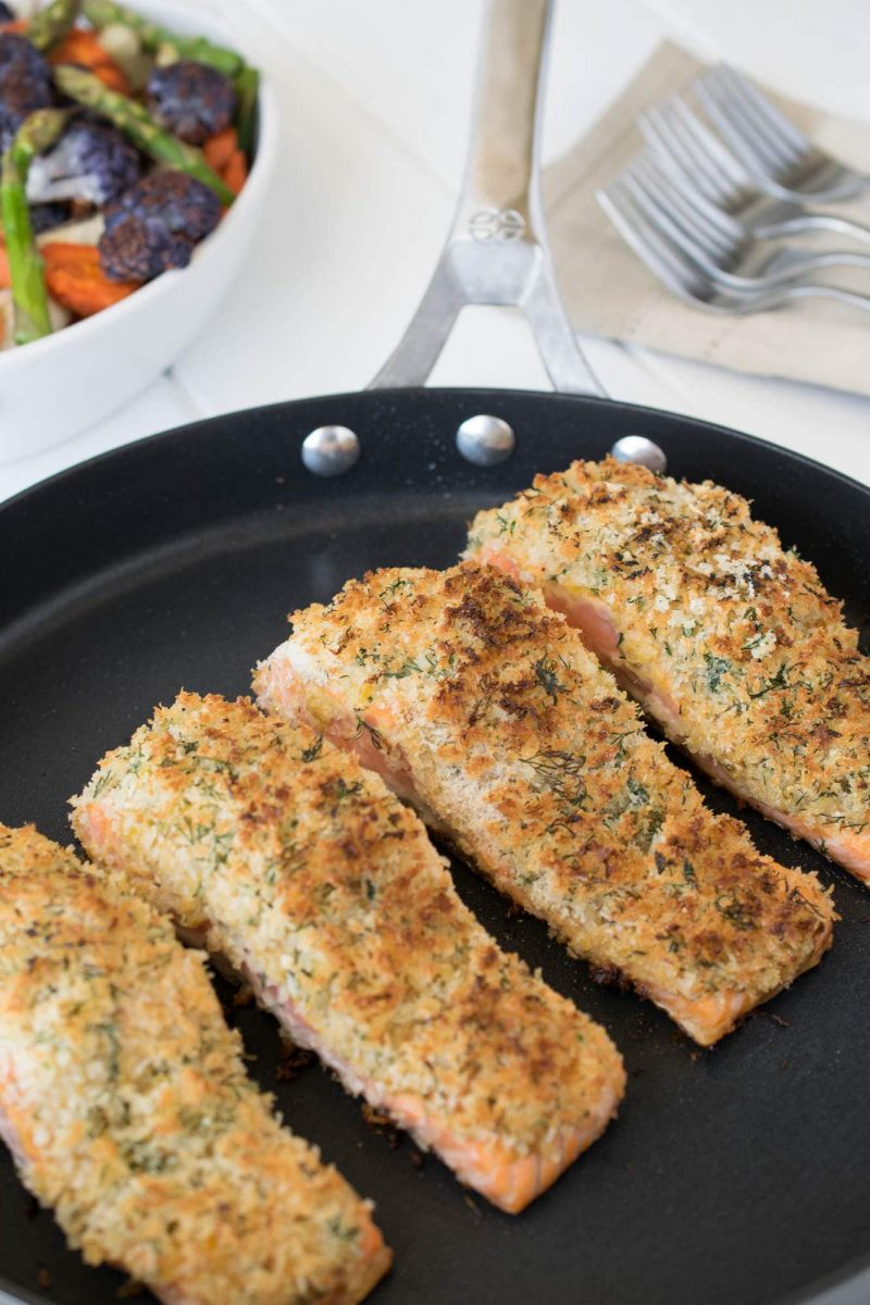 4 Lemon parmesan crusted salmon filets cooking in a large skillet