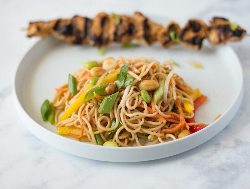 Noodle salad on a white plate with grilled chicken skewer