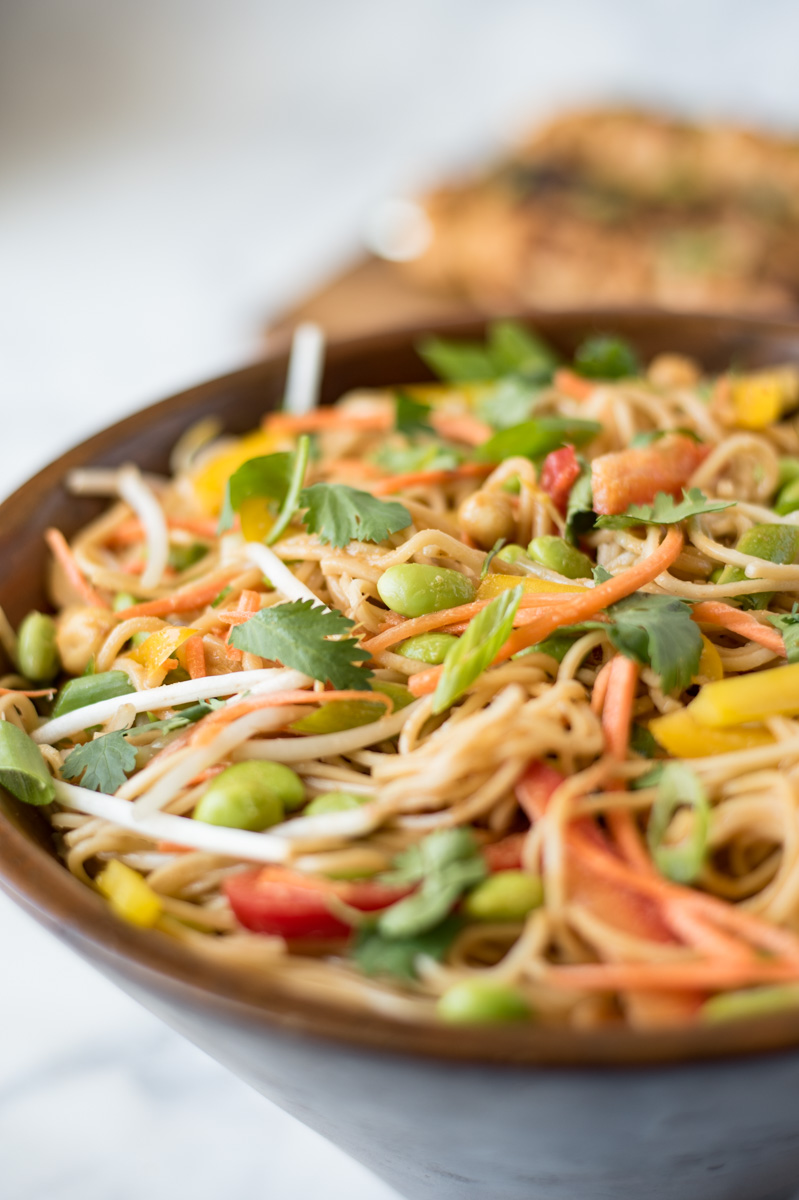 Closeup of a large bowl of lemongrass vegetable noodle salad with colorful vegetables