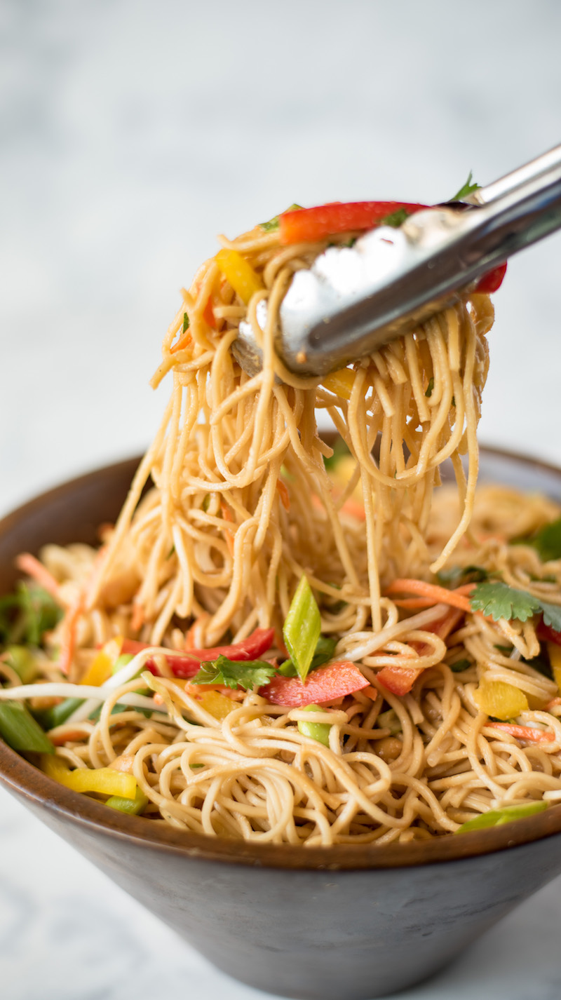 Tongs grabbing noodles from a large bowl of lemongrass vegetable noodle salad