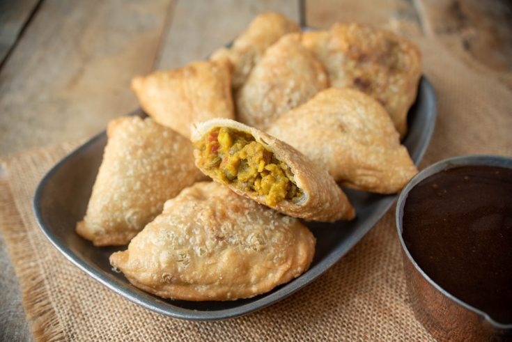 A cut open samosa showing the lentil curry filling laying on a plate with other samosa