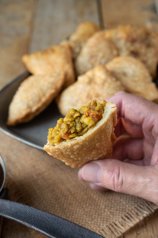 Holding a lentil samosa cut in half showing the filling