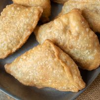 A closeup of samosas lying down showing the browned outside