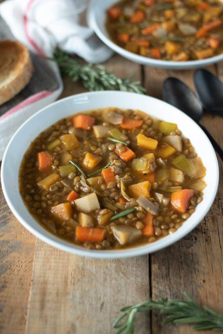 Lentil soup with winter vegetables in a white bowl with spoons and fresh rosemary