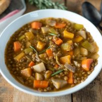 Lentil soup with winter vegetables served in a white bowl with 2 spoons and toasted bread