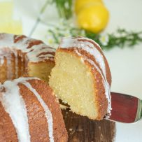 Lifting a slice of limoncello pound cake from a whole bundt cake