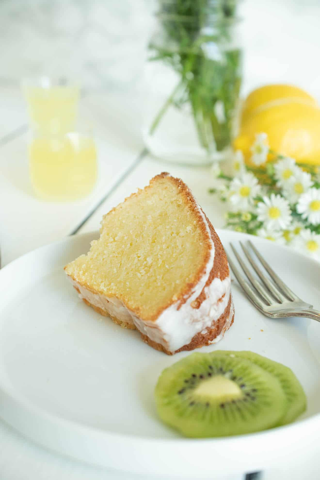 A slice of limoncello pound cake on a white plate with a fork and slices of kiwi