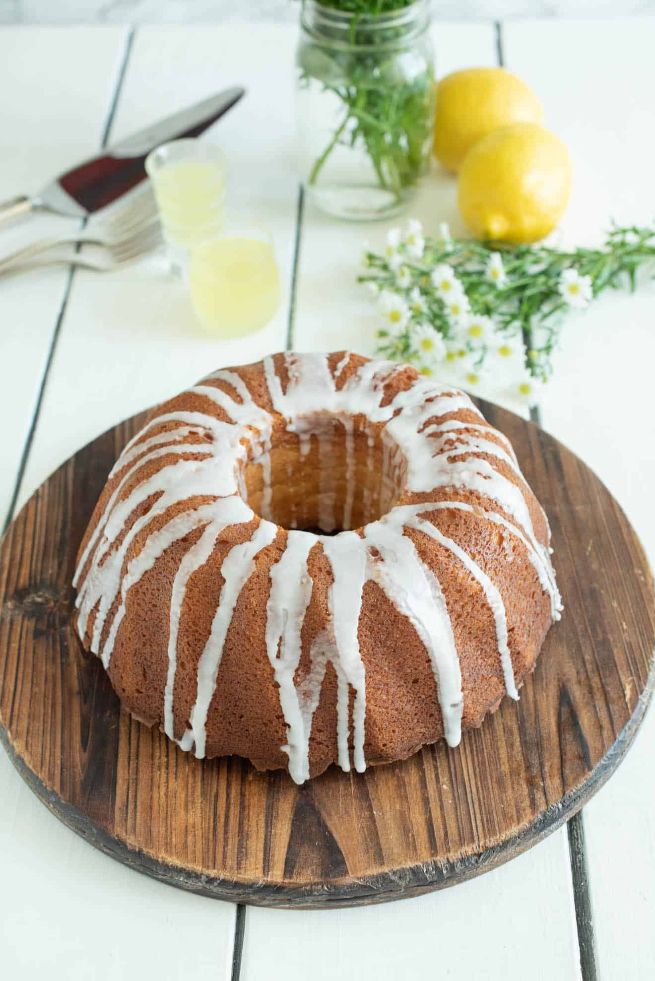 A whole bundt cake drizzled with frosting on a round, wood cake stand with lemons and daisies in the background