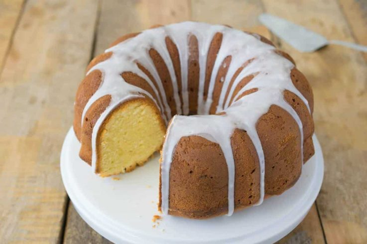 A limoncello pound cake on a cake stand drizzled with white glaze