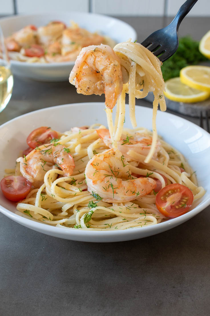 Grabbing a bite of pasta and shrimp on a fork