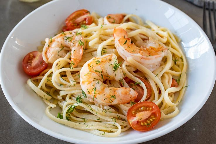 Meaty shrimp served over linguine with tomatoes and dill in a white bowl