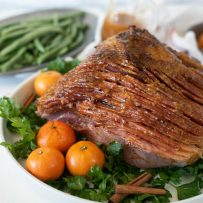 Mandarin Orange Spiced Glazed Ham presented and ready to serve on a bed of parsley with a side of green beans and sweet mashed potatoes