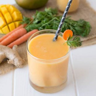 Smoothie in a short glass with a straw with fresh ginger, carrots and mango