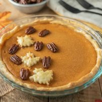 Maple Sweet Potato Pie in a glass pie pan garnished with pastry maple leaves and maple glazed pecans