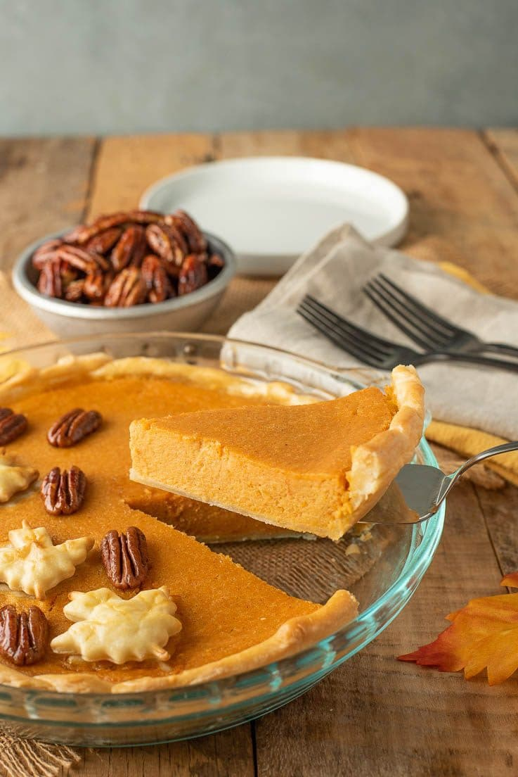 A slice of pie being served with forks and plates and extra maple glazed pecans