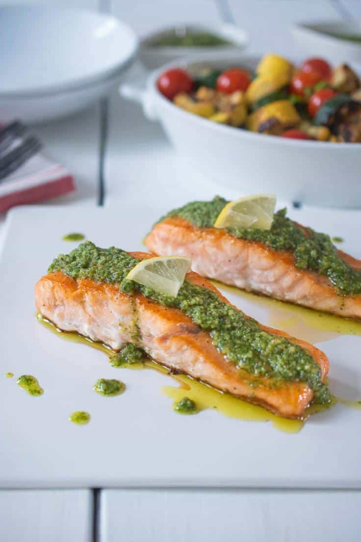 2 salmon filets on a white plate with pesto and lemon