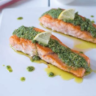 Mediterranean pesto salmon served on a white platter garnished with lemon