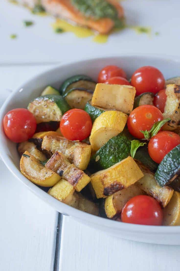Zucchini and tomatoes in a white bowl