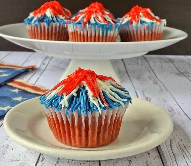 Red velvet cupcakes adorned with the red, white and blue. These patriotic, Memorial Day firework cupcakes will be the star of your Memorial Day barbecue.