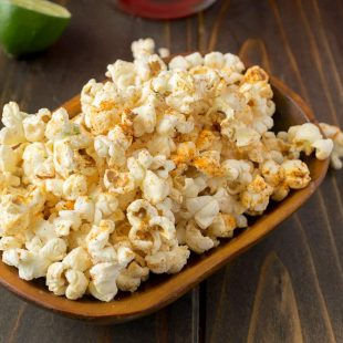 A rectangle bowl of Mexican popcorn with lime wedges