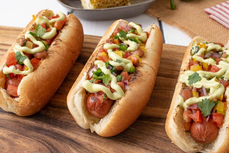 3 Mexican Style Hot Dogs lined up on a board