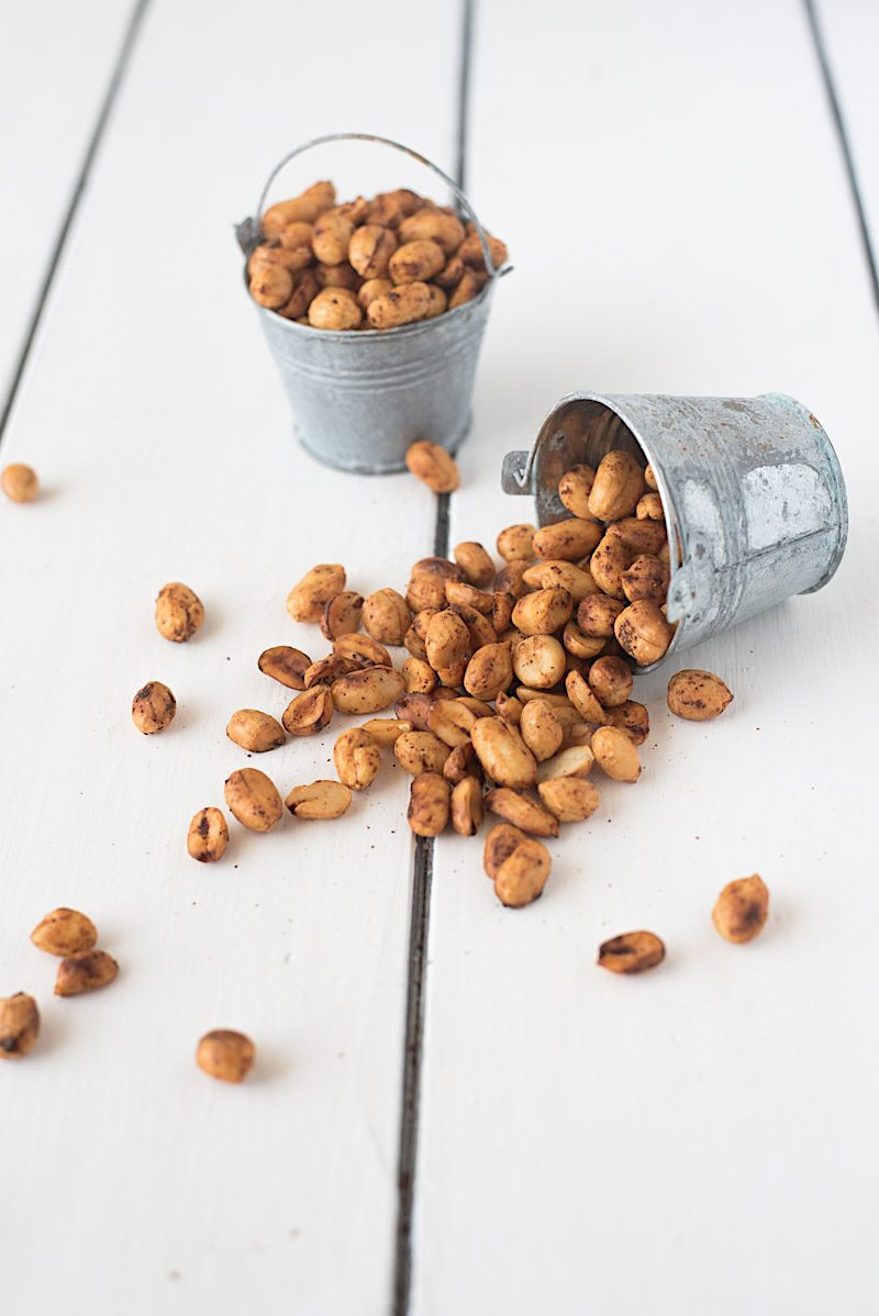 Peanuts in 2 small buckets with one fallen over and nuts spilling out