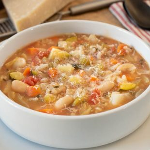 Milanese Minestrone loaded with vegetables and beans in a white bowl