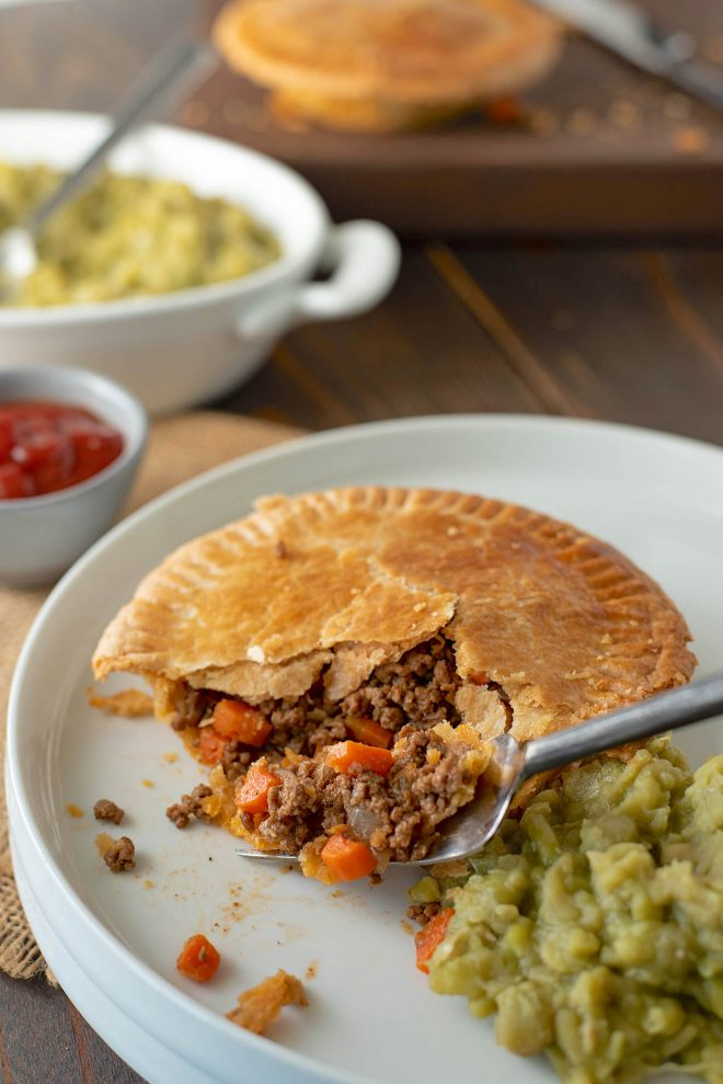 The pie on a white plate with a fork and mushy peas