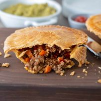 A minced beef and onion pie cut open showing the beef and vegetables inside