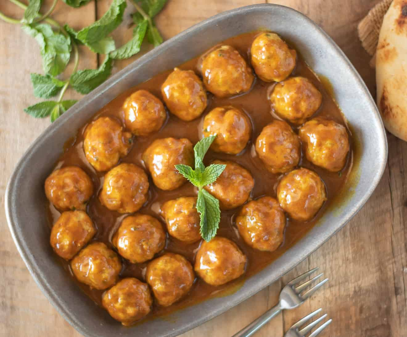 A platter of mini chicken meatballs in a curry sauce