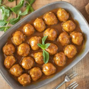 Mini Indian meatballs in a curry coconut sauce served in a pewter bowl